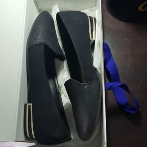 Black loafers with gold heel detail